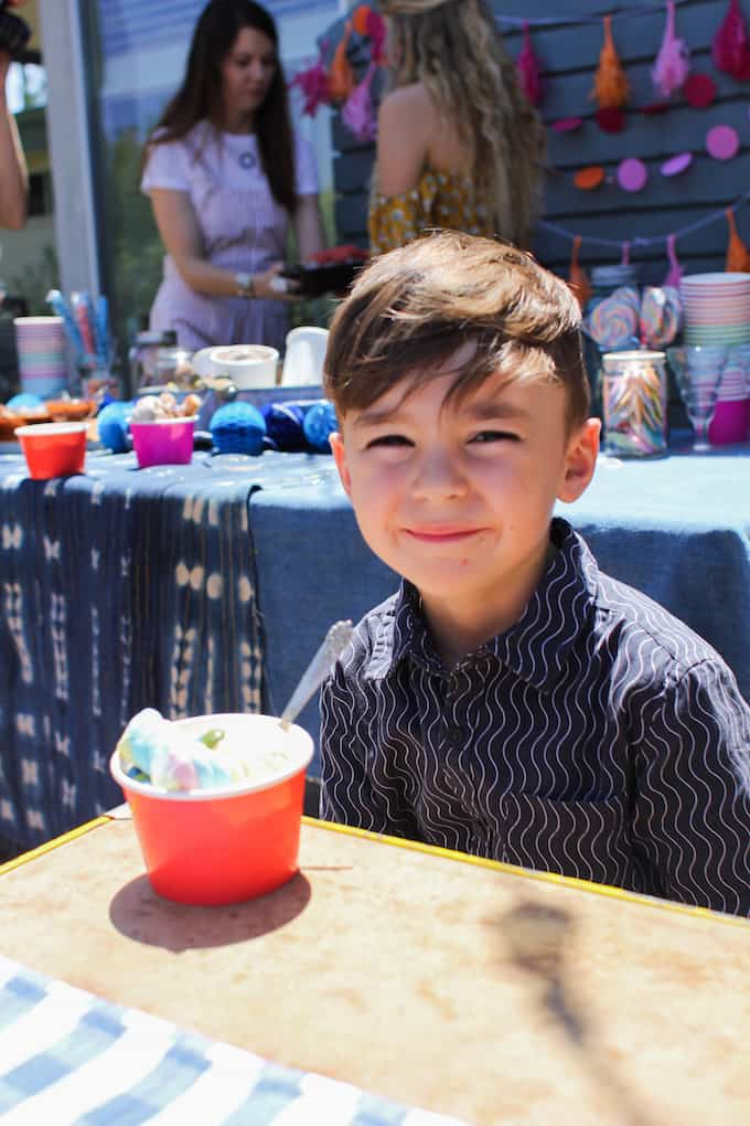 A boy sitting at a table with a cup of ice cream in front of him. A blue checkered table cloth is on the table.
