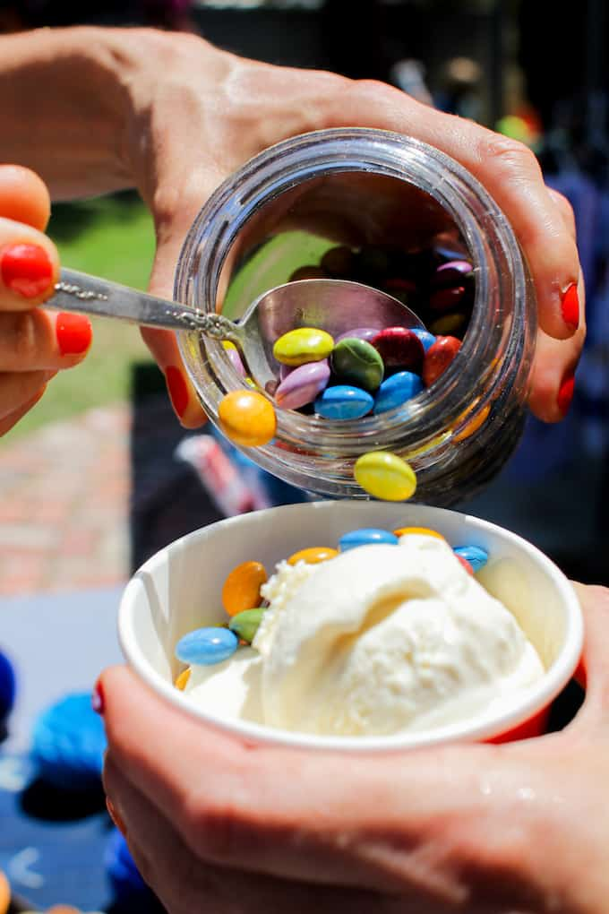 A person holding a cup of cream cheese ice cream and another person spooning M&M's into the cup of ice cream.