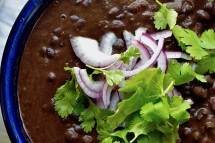A bowl of black beans with cilantro and onions on top.