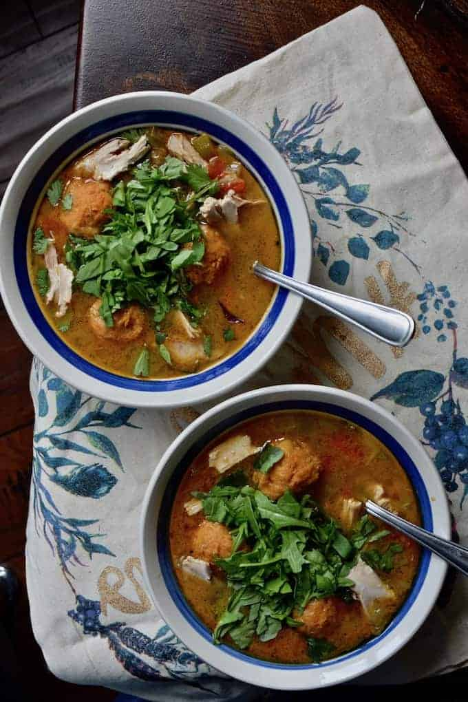 Traditional chicken and dumplings get a Caribbean make over with these smoky mofongo dumplings made with mashed plantains, smoked paprika, and garlic all floating in a rich chicken broth. #mofongo #healthyLatinfood #chickenanddumplings #healthysoup