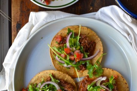 Ultra tender lamb braised in a rich guajillo chile sauce make these lamb tostadas a sophisticated party appetizer or main dish when served with pico de gallo, black beans, and coconut rice. #mexicanrecipe #lambrecipe #tostadarecipe #guajillorecipe #spicyfood