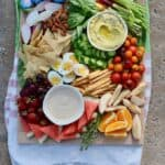 A large cutting board full of food like cut fresh fruit and vegetables and two bowls of dip sitting on a striped towel .