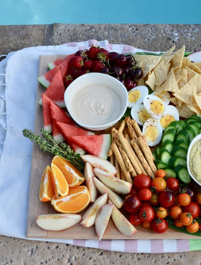 A wooden board filled with fresh fruits and vegetables and bowls of dip sitting next to a pool.