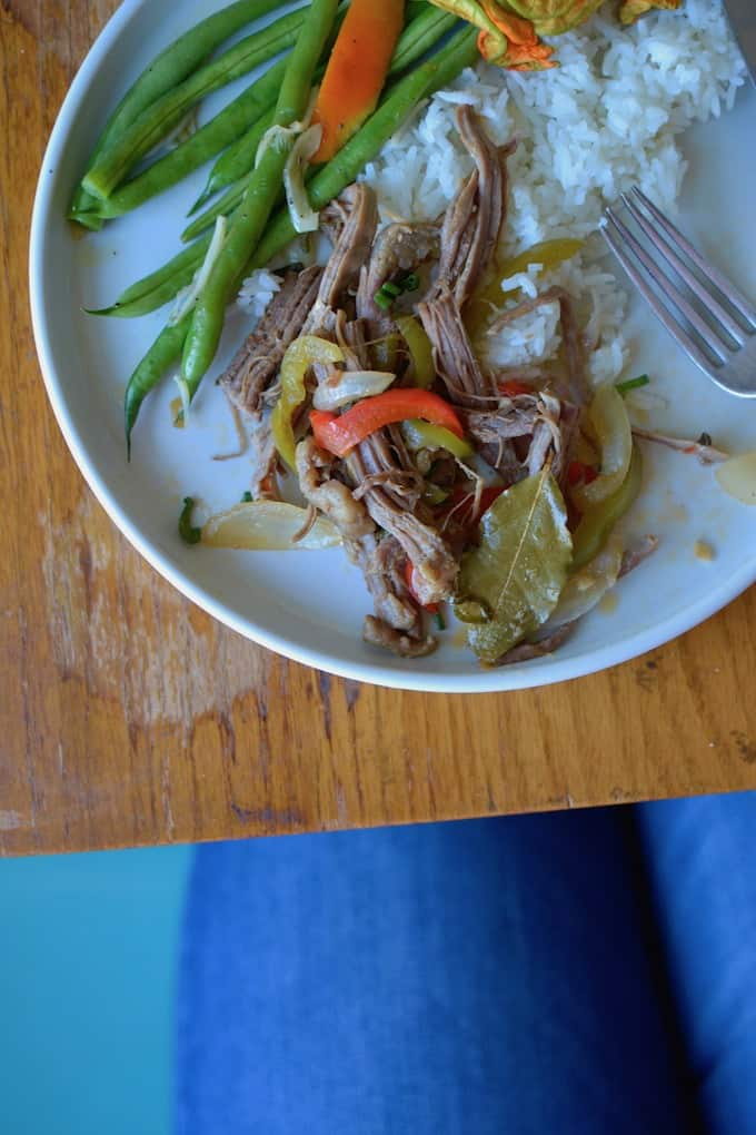 An overhead image of shredded meat, peppers, onions, and bay leaf on a white plate with rice and green beans.
