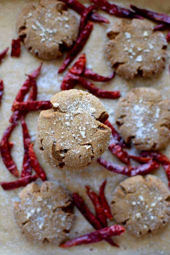 Chewy, extra spicy molasses crinkle cookies with the warm spices we all love and an extra kick from ground arbol chili powder. These soft ginger cookies are made with coconut oil so they're dairy free and get a special sprinkle of vanilla bean salt too! #spicymolassescookies #molassescookies #gingersnapcookies #gingerbreadcookies #chewycookies #christmascookies