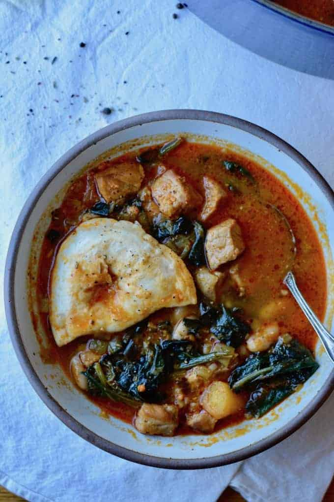 #ad|Rustic Spanish Pork & Pierogy Stew in a smoked paprika, orange, and garlic broth with white beans. Baked Classic Onion Pierogies dot each bowl for a crunchy finish. #spanishporkstew #pierogies #MrsTspierogies #porkstew