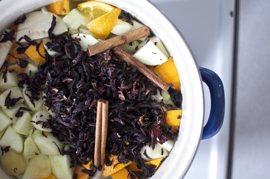 Dried hibiscus flowers, cinnamon stick, oranges, and other fruits in a large pot with a blue handle.