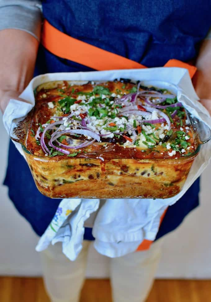 Person in a blue apron with an orange tie holding a baking dish of Mexican lasagna, and a white kitchen towel.