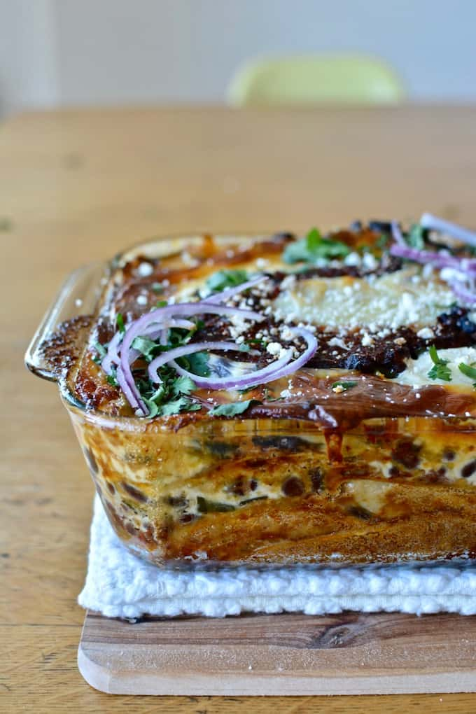 Side view of baked Mexican casserole with layers of tortillas, cheese, black beans, sauce, and sliced red onions on top.