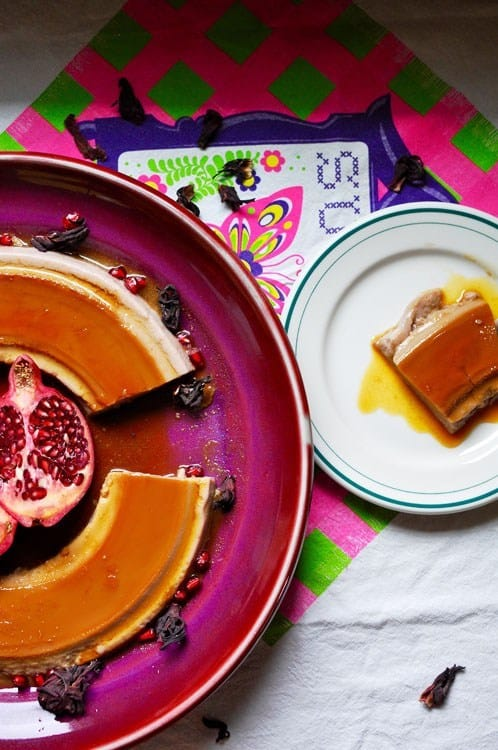 A large purple plate with a flan on it. There is a piece missing from the flan and the piece is sitting on a plate next to it.
