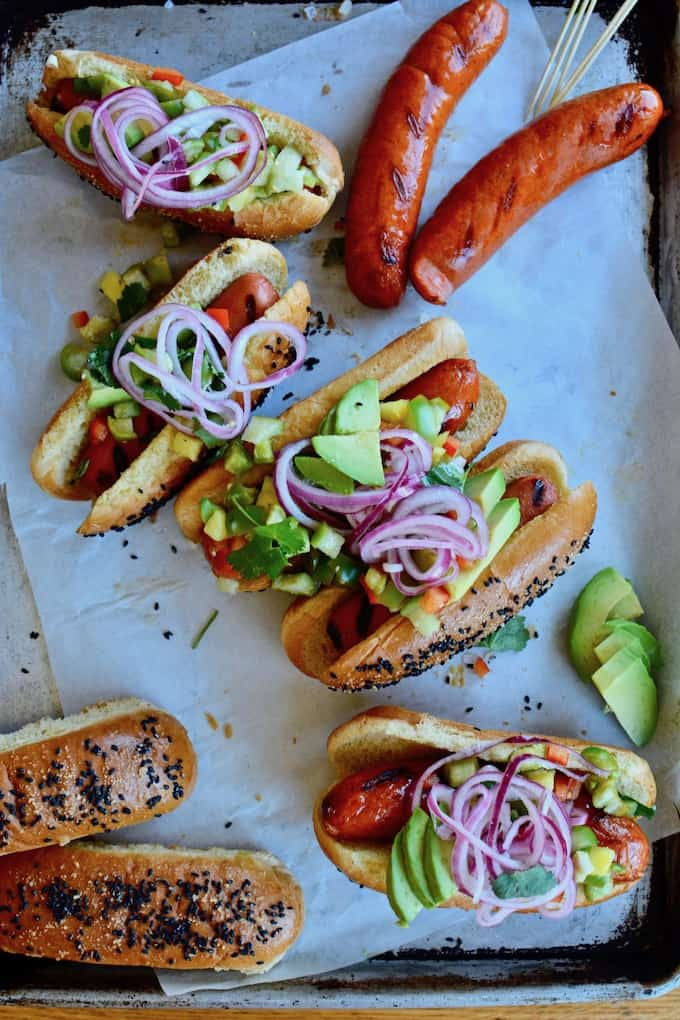 Grilled hot dogs have never had it so good: Black sesame brioche buns, homemade tomatillo-pineapple pickle relish, pickled red onions, and sliced avocado. #hotdogs #picklerelish #spicypicklerelish #hotdogtoppings #grillingrecipes