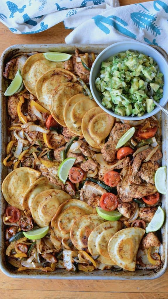 #ad| Our new favorite sheet pan chicken fajitas feature Cheddar Pierogies, chicken, and veggies tossed in chipotle spice mix + avocado pico de gallo for the win! #sheetpandinner #chickenfajitas #pierogies #avocado #sheetpanfajitas