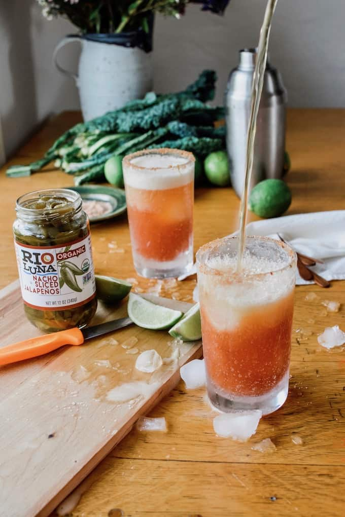 #ad|This is the best authentic Mexican Spicy Jalapeño Michelada beer cocktail you will ever try, flavored with fiery pickling liquid from the peppers and a whole pile of jalapeños and lime. #michelada #jalapenos #beercocktail #beer #spicycocktail