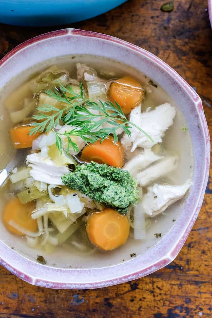 This chicken and leek soup is so easy to make, just toss everything in a big pot and let simmer. It is light, but comforting with ginger and mint then topped with a bold pesto made from carrot tops, radish tops, and lemon zest. #chickensoup #leeks #pesto #chickenandleeksoup #carrottops