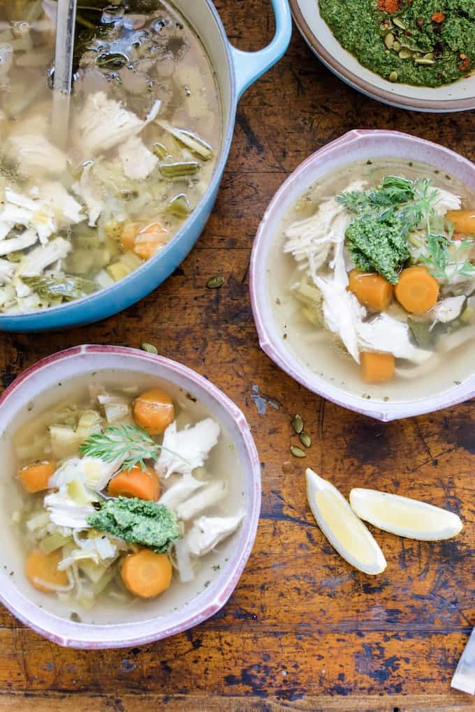 This chicken and leek soup is light, but comforting with ginger and mint then topped with a bold pesto made from carrot tops, radish tops, and lemon zest. #chickensoup #leeks #pesto #chickenandleeksoup #carrottops