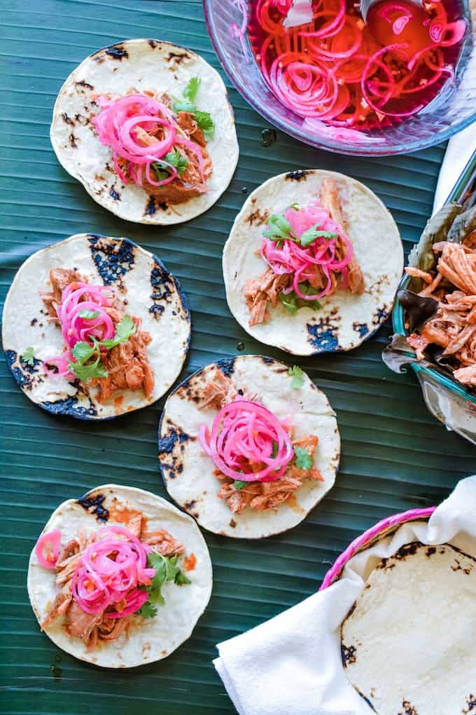 Toasted corn tortillas hold Cochinita Pibil tacos topped with red onions.
