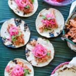 Tacos of Cochinita Pibil laying on a green background next to a basket of tortillas.