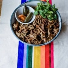 A plate of Instant Pot Carnitas with a small bowl of pickled jalapenos and carrots and a bunch of cilantro sitting inside the bowl sitting on a rainbow placemat.