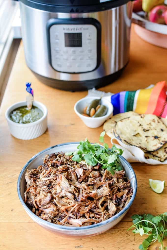A bowl of pork carnitas sitting on a wood table in front of an Instant Pot, some corn tortillas, and two bowls of salsa and pickled jalapenos.