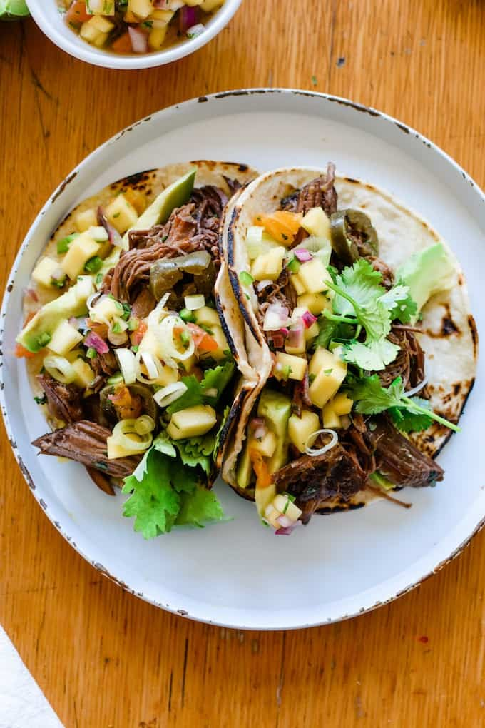 How to make the BEST slow cooker beef tacos with loads of sliced jalapeños and topped with a fruity mango-citrus salsa. #tacorecipe #beeftacos #slowcookerrecipe #slowcookerbeeftacos #mexicanfoodrecipe
