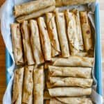 A blue pan with parchment paper in it, filled with beef flautas sitting on a wooden table.