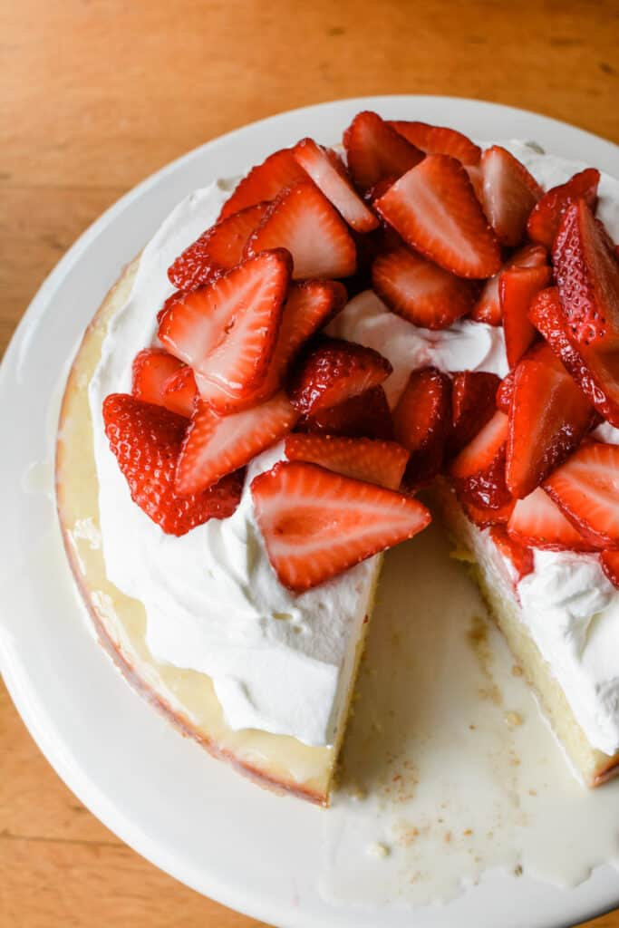 Tres Leches cake is one of my all-time favorite desserts. Here I made it with a twist by substituting Meyer lemon butter cake for the traditional sponge and topping it with sweet cream and berries. #tresleches #cakerecipe #strawberries #strawberryshortcake