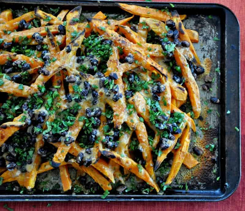 My most popular recipe(not to mention one of my favorite easy Mexican dishes): Easy, 4-ingredient sweet potato nachos! Baked sweet potato fries get topped with black beans, smoked cheddar cheese, and cilantro. Perfect for a Stay-At-Home Cinco de Mayo party. #cincodemayoparty #cincodemayo #nachos #sweetpotato