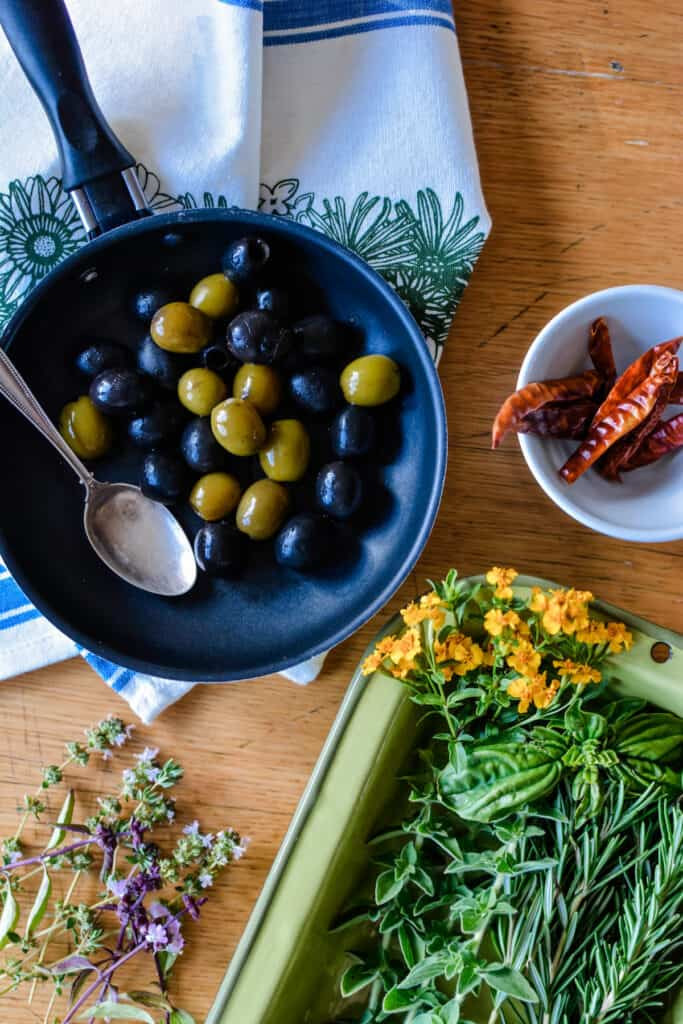 Small pan of olives sitting on a wooden table with a bowl of chiles sitting next to it and a tray of herbs.