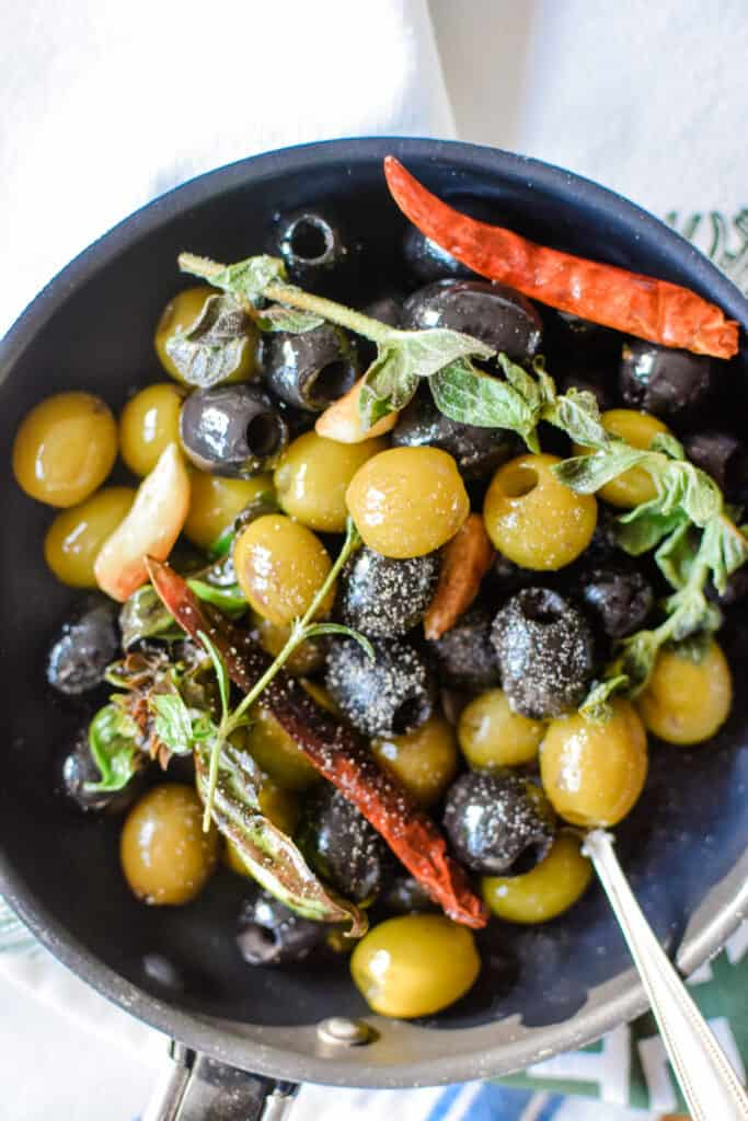 Close up of green and black olives in a pan with fresh oregano sprig, dried chiles, and a spoon.