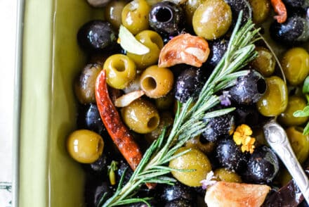 Olive Lovers Unite! You've got to try these Spicy Marinated Olives with fiery dried arbol chiles, pan-roasted cloves of garlic and loads of fresh herbs like rosemary and oregano. Fix this when you need a quick, easy & comforting appetizer to share with friends that will disappear in minutes. Serve warm or make ahead and serve room temperature with slices of crusty baguette for scooping. {gluten-free, grain-free, and vegan} #olives #marinatedolives #spicy #appetizer #roastedgarlic #easyappetizer