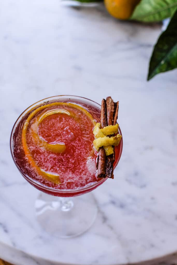 A Pomegranate cocktail sitting on a marble table with a cinnamon stick garnish