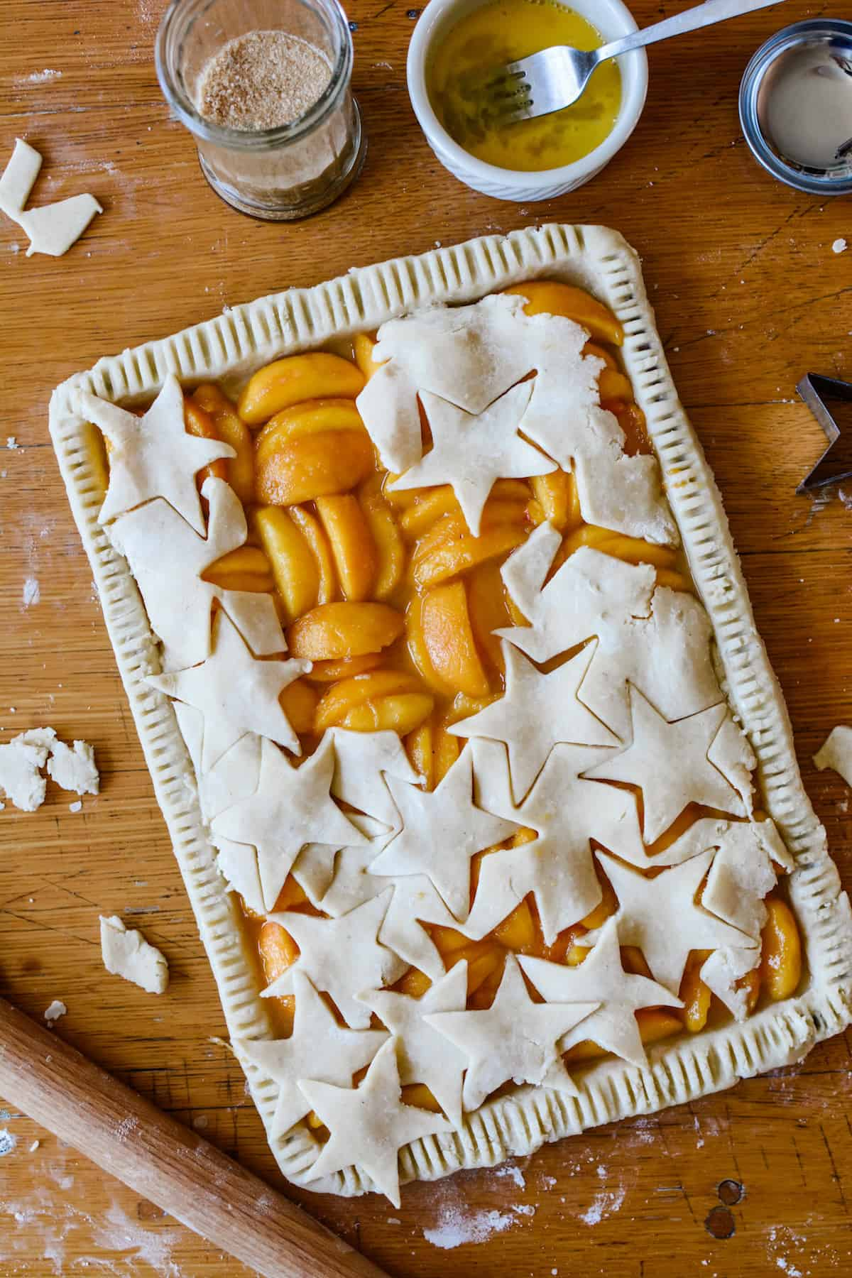 A peach slab pie sitting on a wooden table with a rolling pin and scraps of dough.