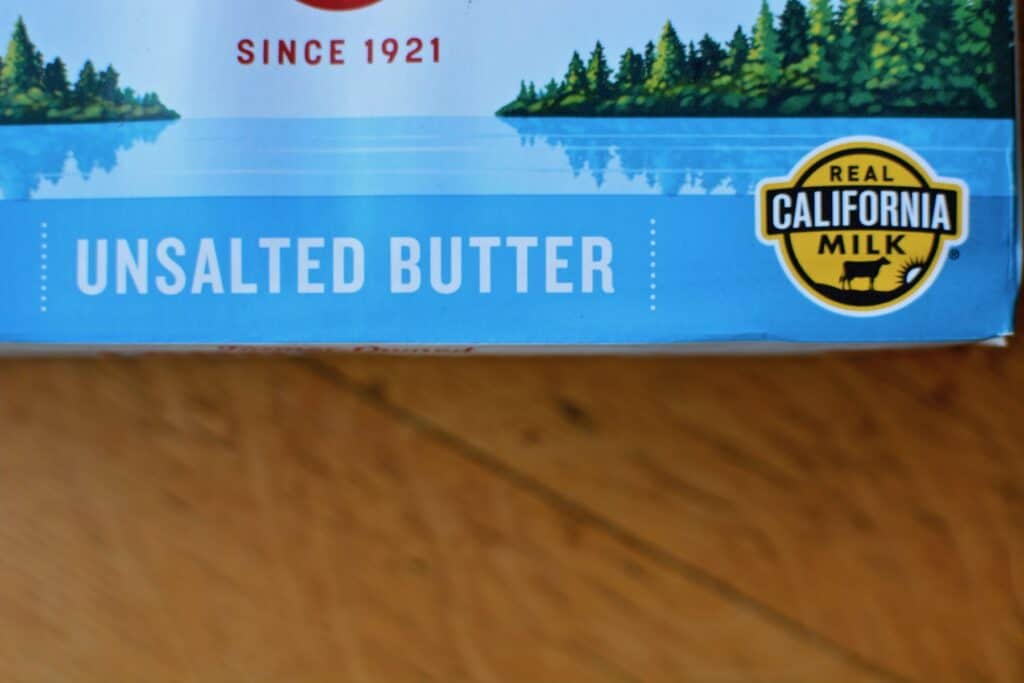 A package of butter with the Real California Milk seal sitting on a wooden table.