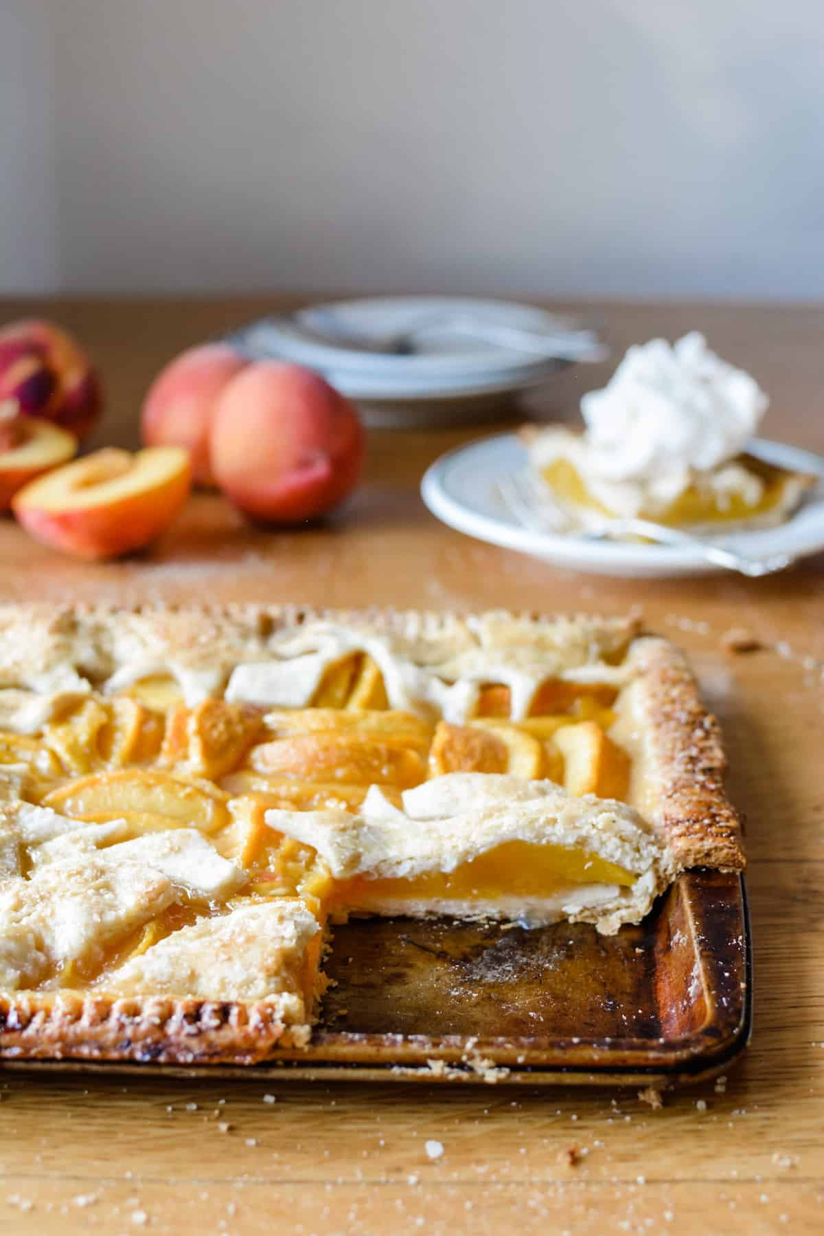 Peach pie with a piece missing sitting on a wooden table with a piece on a plate in the background.
