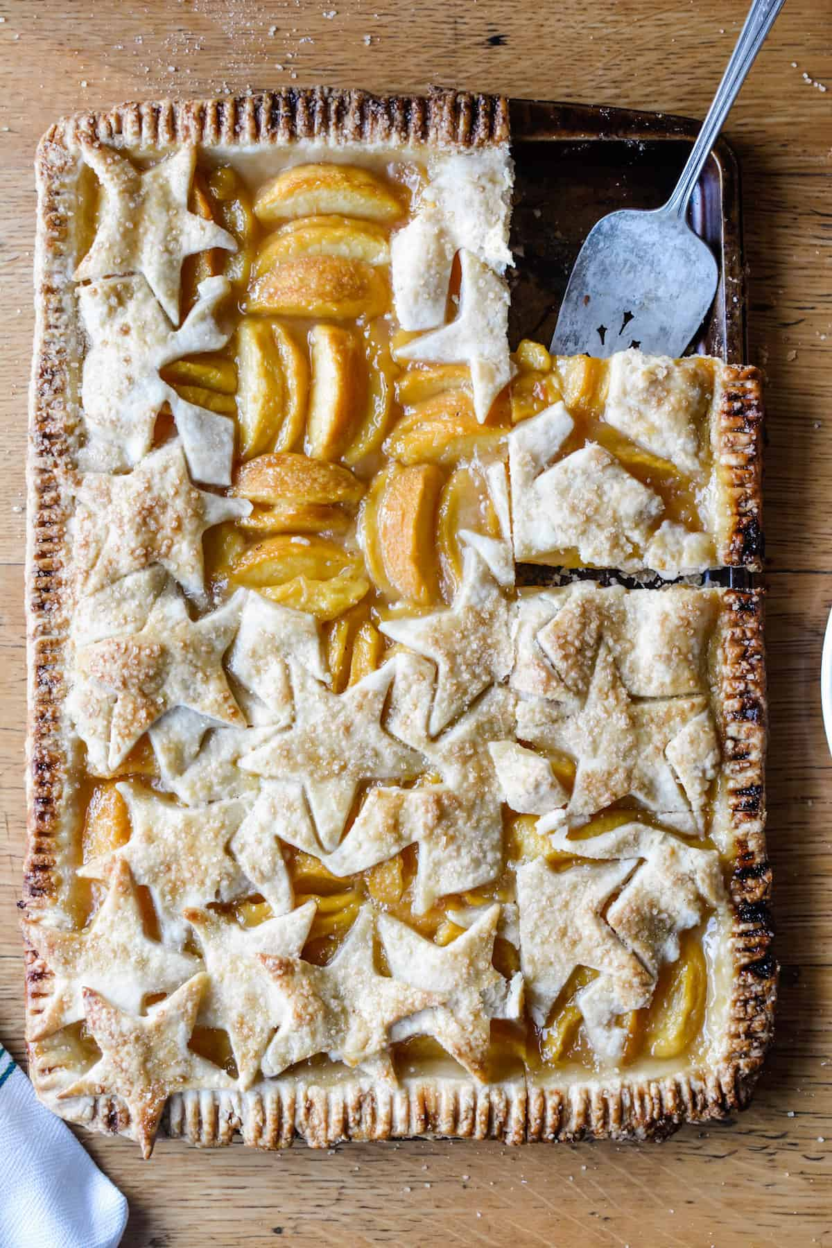 This Fresh Peach Slab Pie takes summer's juciest peaches and makes a HUGE pie complete with the most perfectly crisp, buttery crust flavored with nutmeg. #slabpie #peachpie #piecrust #pierecipe