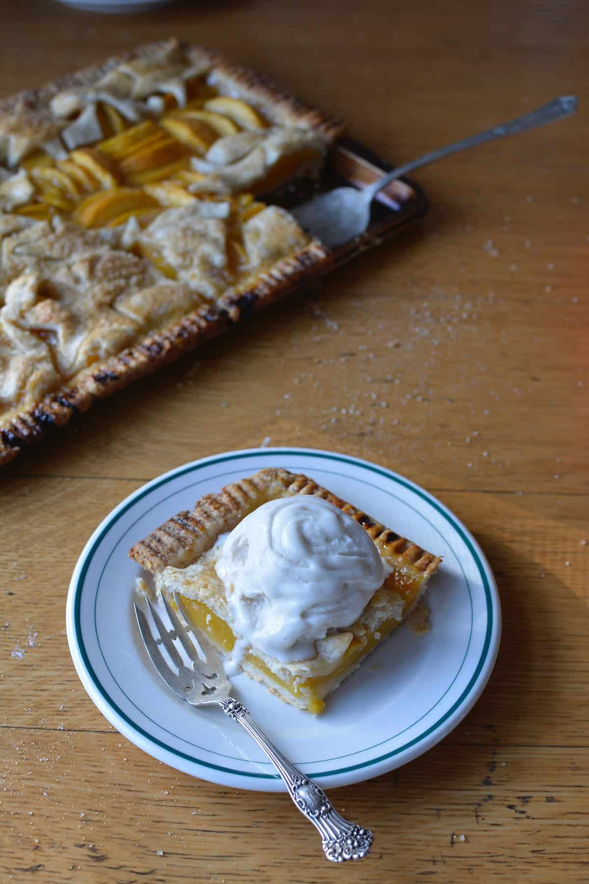 A piece of pie on a plate with a scoop of vanilla ice cream on top and a fork next to it sitting on a wooden table.