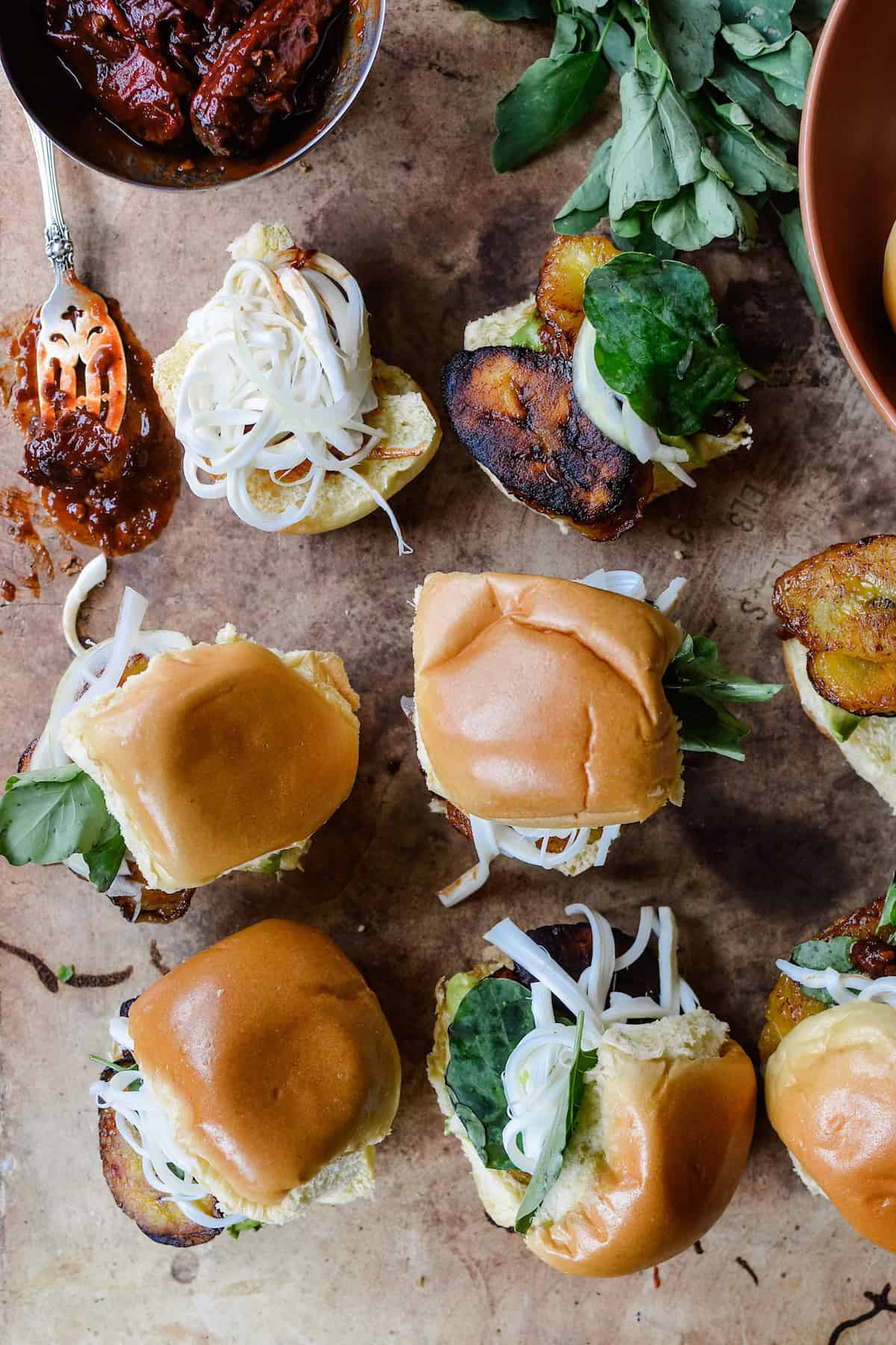 This plant-based version of a Cemita Poblana sandwich swaps classic milanesa for fried plantain and the sesame bun for brioche slider rolls.