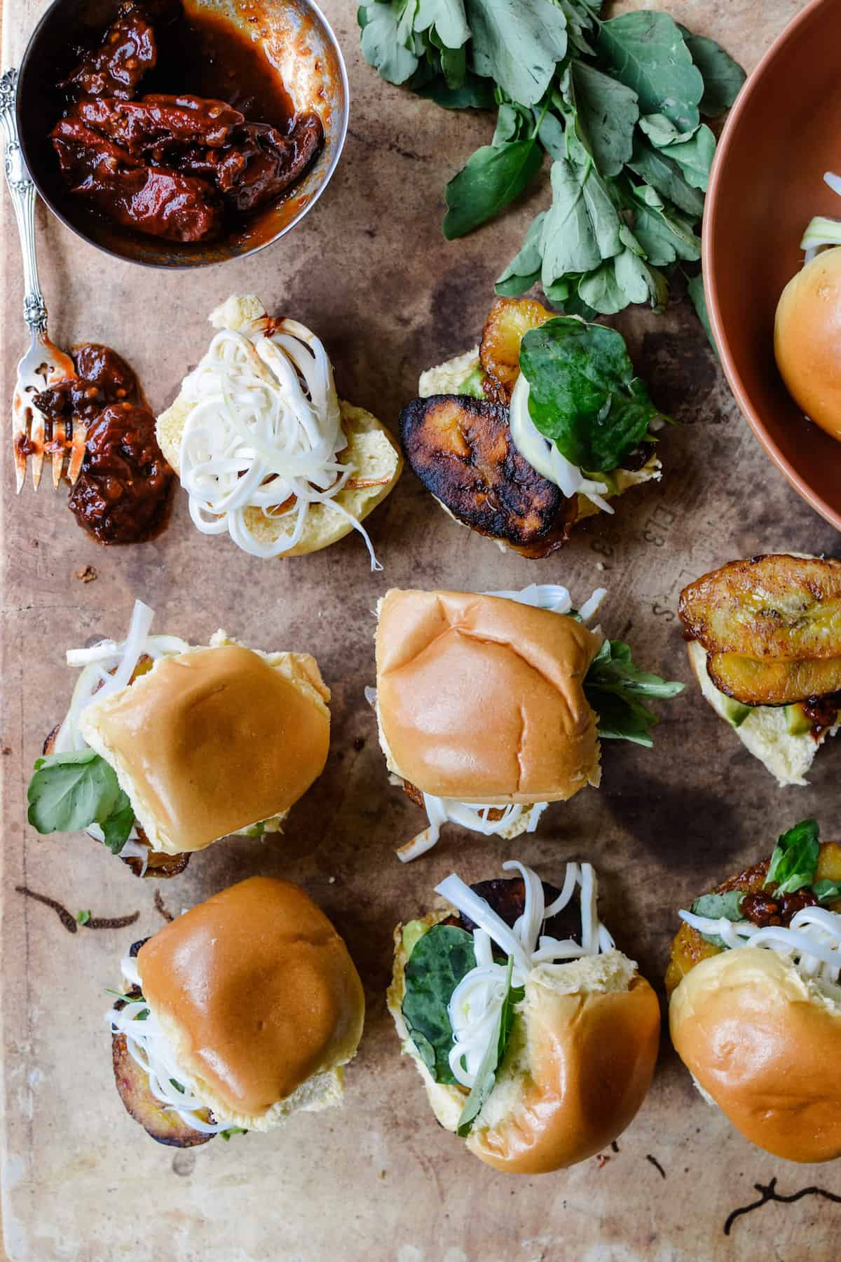 Several slider sandwiches sitting on a table next to green Papalo leaves and a metal dish of chipotle peppers in adobo sauce sitting near by.