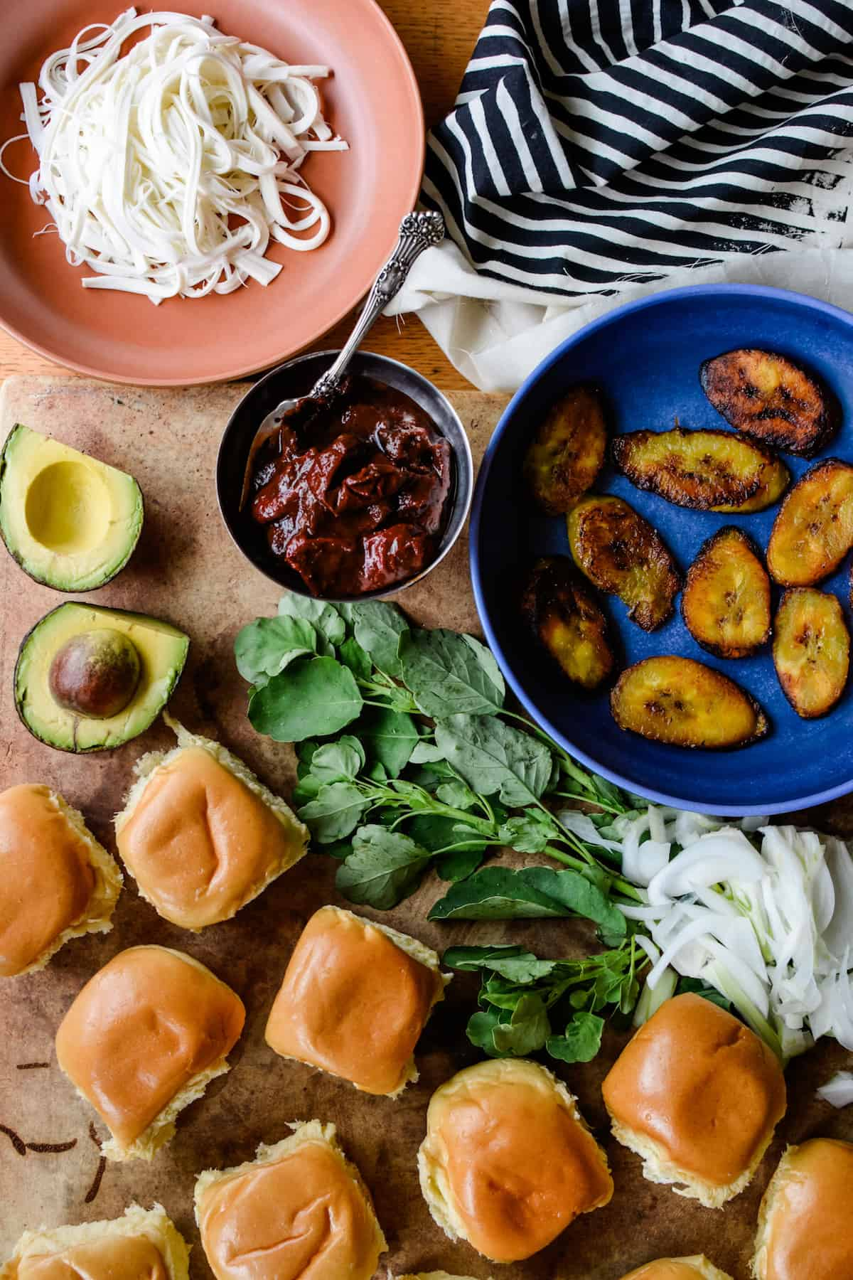 Slider rolls, a halved avocado, a plate of Queso Oaxaca, chipotles, and a dish of fried plantains on a table.