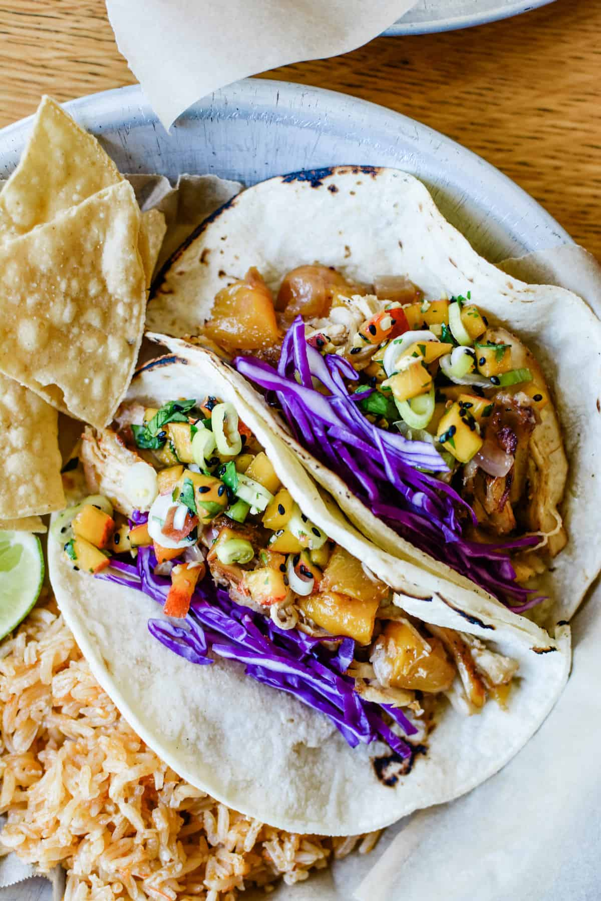 Fresh peaches simmer with chicken in the Instant Pot in mere minutes and then quickly fry in the Air Fryer for crisp edges. Serve with a peach-ginger salsa! #tacos #chickencarnitas #instantpot #peaches