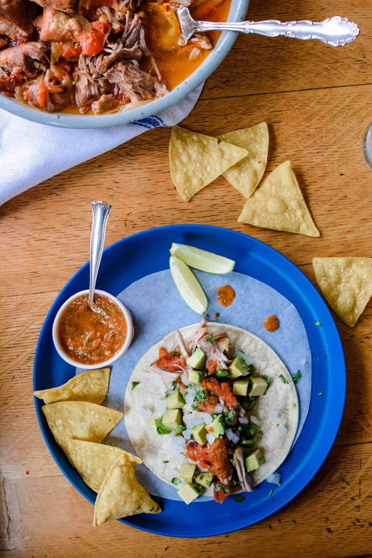 A blue plate with a pork Tinga taco on it, tortilla chips on the side, and small dish of salsa with a spoon in the dish. A few more chips are scattered on the table.