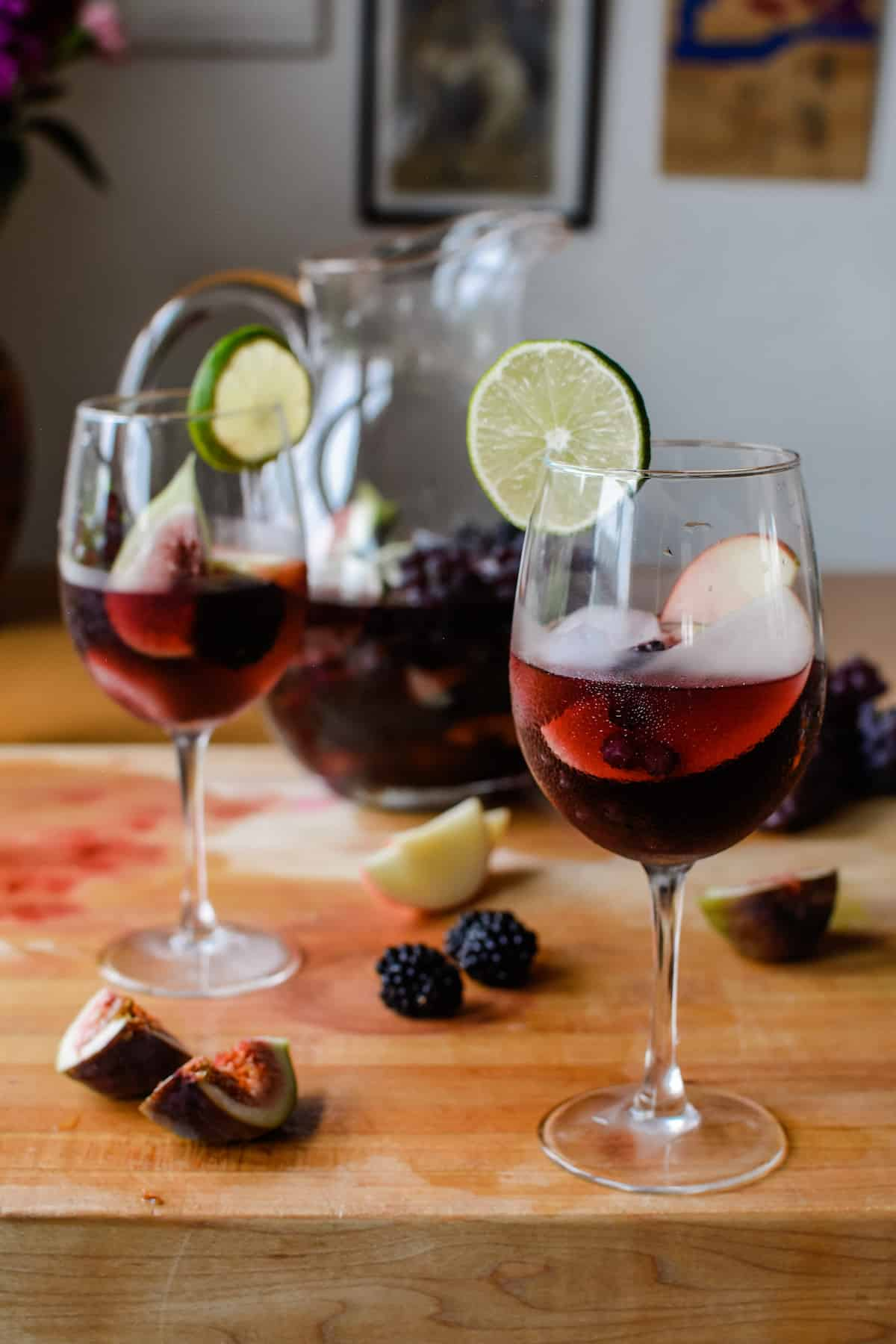 Two wine glasses of sangria and ice with a lime wedge on each glass. Glasses are sitting on a wooden cutting board next to cut fruit.
