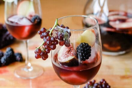 This Fall Sangria is like the California wine harvest in a glass: Champagne grapes, Mission figs, crisp apples, and blackberries mixed with luscious Merlot. #sangria #winecocktails #redwinesangria #fallsangria