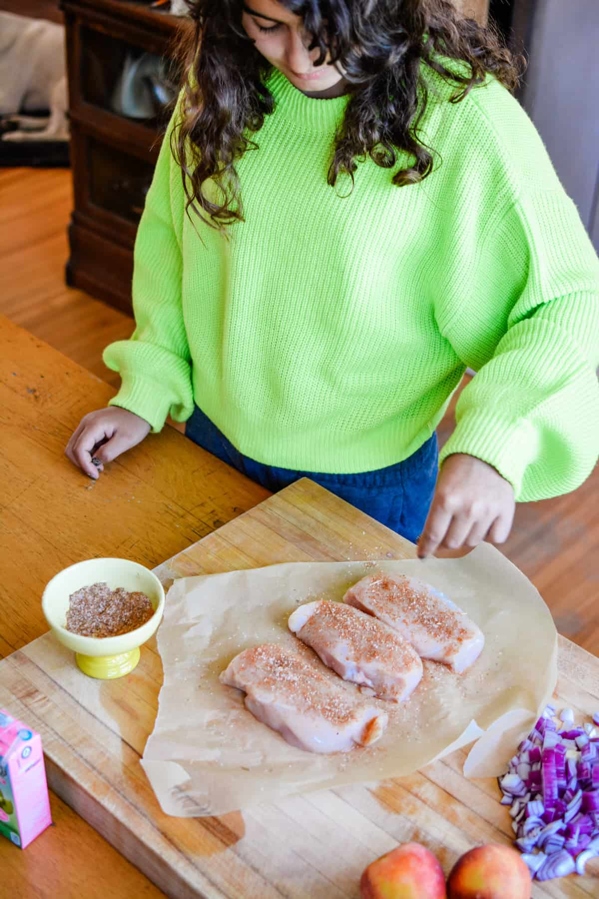 Girl sprinkling spice rub on chicken breasts sitting on a piece of parchment paper on a wooden cutting board.