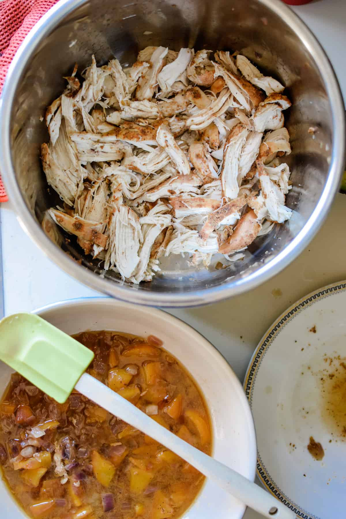A metal pot with shredded chicken sitting next to a ceramic bowl with cooked peaches and onions in broth and an empty plate on the side.