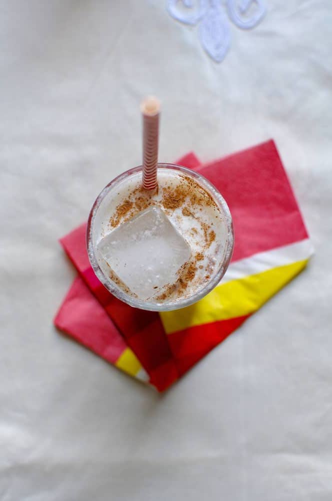 An overhead image of a glass with ice and a milky, white liquid with a dusting of cinnamon and a striped straw sticking out the top.