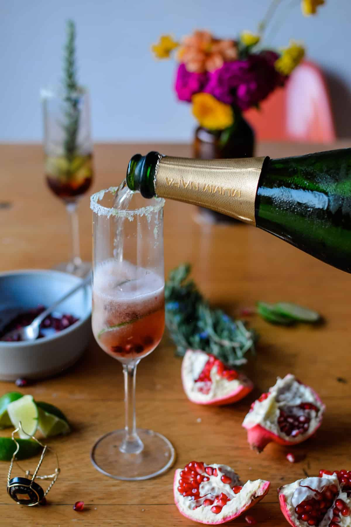 A champgane flute sitting on a wood table with pomegranates and lime slices in it and a bottle of sparkling wine pouring wine into it.