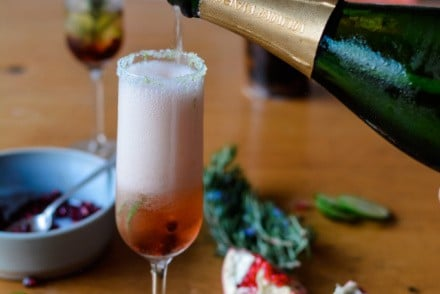 Festive Kir Royale Cocktail using California sparkling wine! This pomegranate sparkling wine cocktail is bubbly and beautiful and the perfect way to toast the holidays. With fresh pomegranate, pomegranate liqueur, and sparkling wine it's an effortless three-ingredient cocktail! #kirroyale #sparklingwine #holidaycocktailrecipe #champagnecocktail #ad