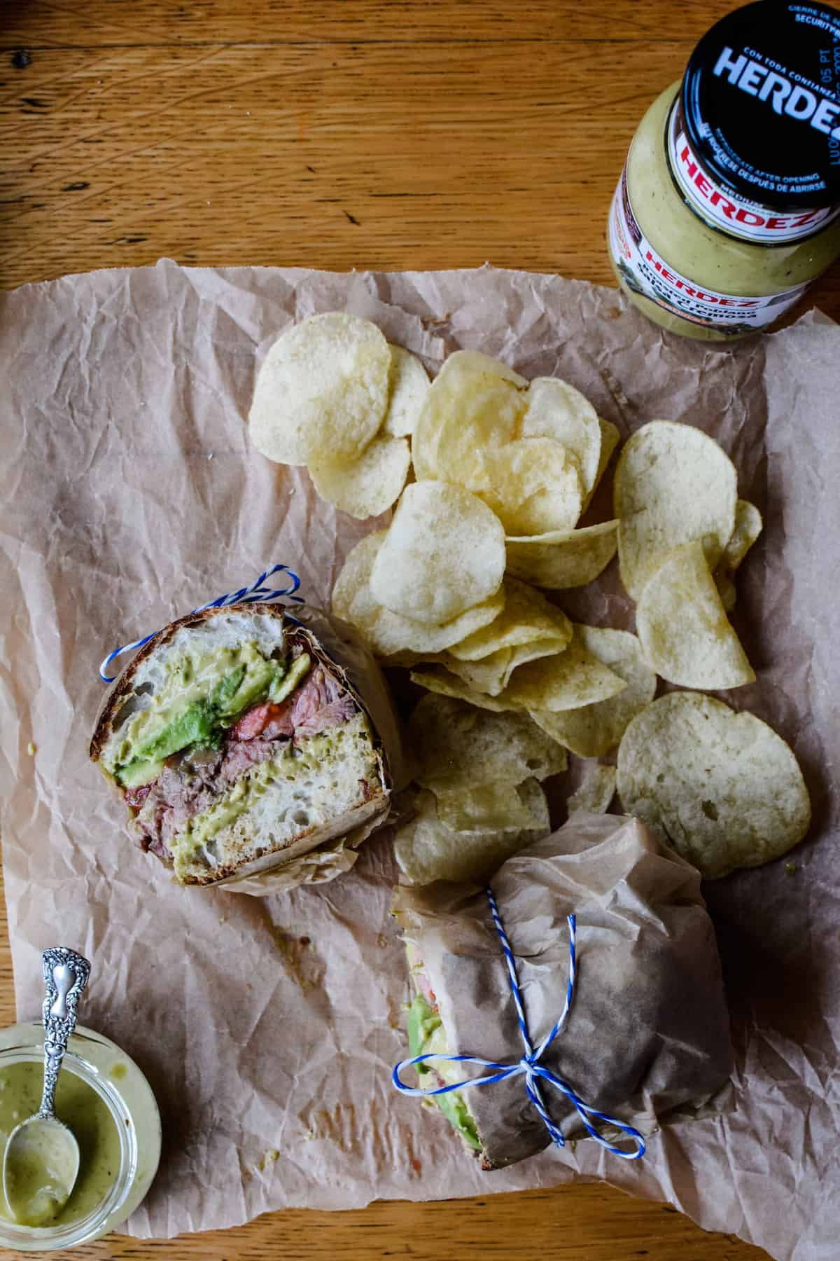 A sandwich sitting on a piece of brown parchment paper surrounded by chips.