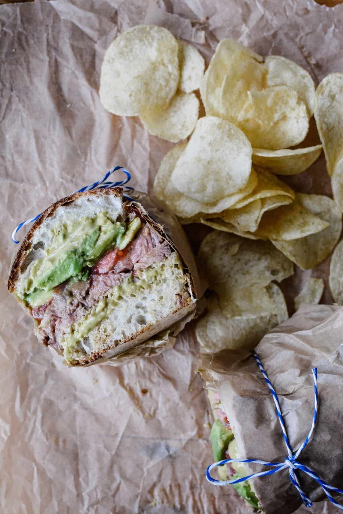 A carne asada torta cut in half sitting on brown parchment paper with chips on the side. The sandwich halves are wrapped in paper with blue and white string around them.